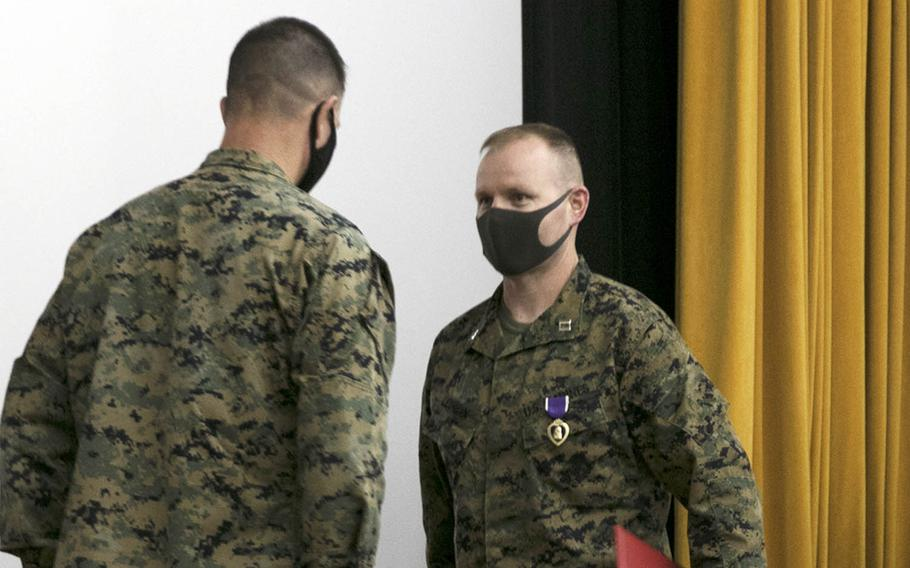Marine Capt. Kevin Leishman receives a Purple Heart from Brig. Gen. Kyle Ellison, commander of the 3rd Marine Expeditionary Brigade, at Camp Courtney, Okinawa, Wednesday, Feb. 24, 2021.