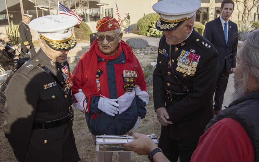 Thomas H. Begay, center, a Navajo Code Talker and Iwo Jima veteran, shows his scrapbook of photos from his time as a Marine to 1st Marine Division commander Maj. Gen. Robert F. Castellvi, left, and I Marine Expeditionary Force commander Lt. Gen. Joseph L. Osterman, right, at a sunset ceremony marking the 75th anniversary of the Battle of Iwo Jima at Marine Corps Base Camp Pendleton, Calif., on Saturday, Feb. 15, 2020.