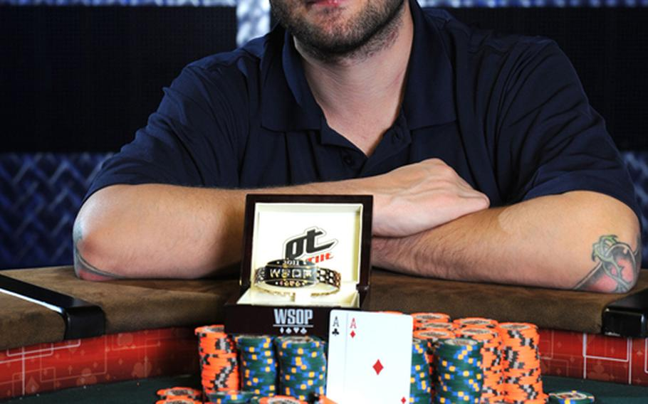 """Former Marine and combat veteran Ken Griffin with his World Series of Poker Gold Bracelet, a large stack of poker chips and his winning hand """"pocket aces"""" after the completion of the WSOP Event 45 in Las Vegas, June 28."""