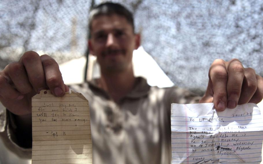 First Lt. Chad Pimley, a 24-year-old forward observer pulling double duty as a civil affairs officer, displays two notes written by Marines and given to Afghans who were requesting compensation for damages.