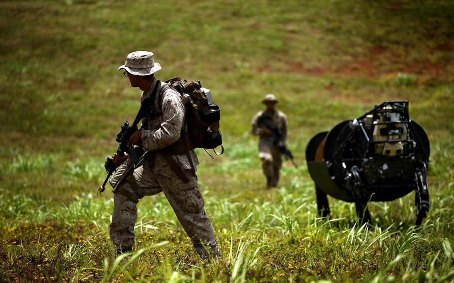Lance Cpl. Brandon Dieckmann and Pfc. Huberth Duarte, of the 3rd Battalion, 3rd Marine Regiment, walk with the Legged Squad Support System, known as BigDog, during a 2014 exercise in Hawaii. The Marine Corps recently shelved plans to field the robot, a 240-pound machine capable of carrying 400 pounds of supplies for troops on patrol.