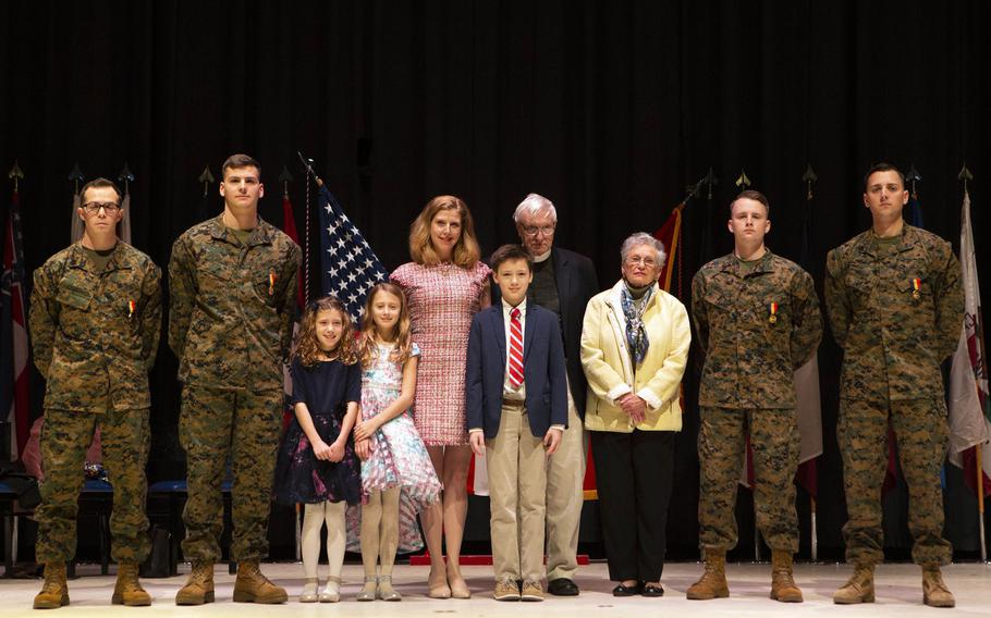 Staff Sgt. Leary Reichartwarfel, left, Sgt. Anders Larson, Cpl. Austin McMullen and Cpl. Timothy Watson pose for a photo with the family they saved after receiving the Navy and Marine Corps Medal at Marine Corps Air Station Cherry Point, N.C., January 28, 2020.