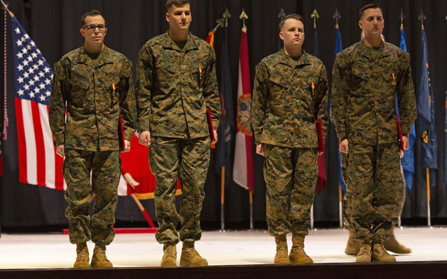 Staff Sgt. Leary Reichartwarfel, Sgt. Anders Larson, Cpl. Austin McMullen and Cpl. Timothy Watson pose for a photo after receiving the Navy and Marine Corps Medal at Marine Corps Air Station Cherry Point, N.C., January 28, 2020.