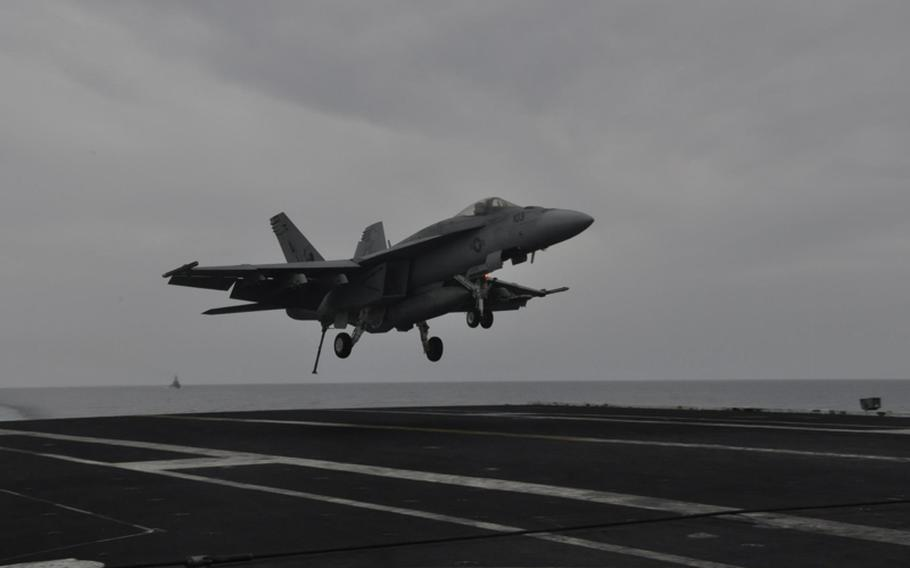 A Navy jet comes in for a landing on the aircraft carrier USS George H.W. Bush on Friday as the ship travels in the Mediterranean Sea.