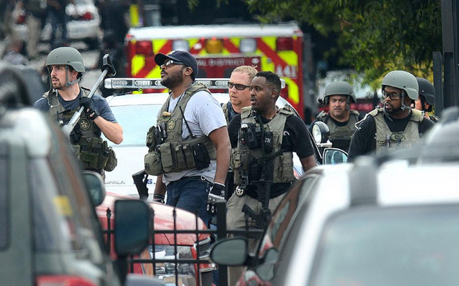 Law enforcement personnel respond to an attack on office workers at Washington Navy Yard on Monday morning, September 16, 2013. A gunman opened fire and killed at least 12 in the attack in Washington, D.C.