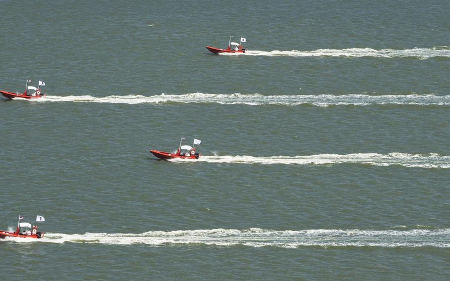 This Tuesday Aug. 12, 2014 photo provided by the U.S. Navy shows an Four unmanned remotely operated high-speed maneuvering surface targets as they  move to their blocking positions during an Office of Naval Research demonstration of autonomous swarmboat technology  on the James River in Newport News, Va.