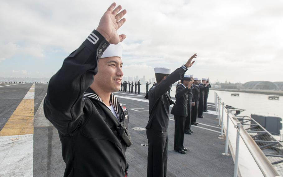 Sailors wave goodbye while manning the rails aboard the aircraft carrier USS John C. Stennis in January. Sailors have been given a one-year extension for receiving extra pay for deployments away from homeport of more than 220 consecutive days.
