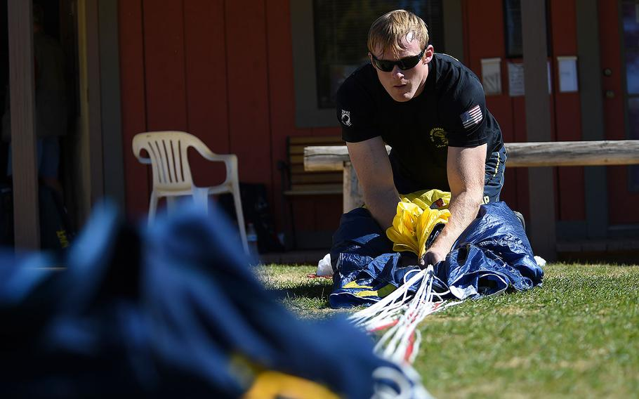 Petty Officer 1st Class Remington Peters, a member of the U.S. Parachute Team, the Leap Frogs, packs his parachute after a practice demonstration in Eloy, Arizona on Feb. 9, 2016.