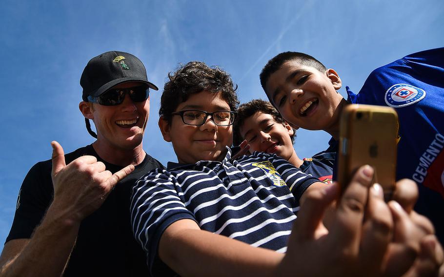 """Petty Officer 1st Class Remington Peters, a member of the U.S. Navy Parachute Team """"The Leap Frogs,"""" poses with students for a selfie after a demonstration jump at Hedenkamp Elementary School in Chula Vista, California on March 3, 2016."""