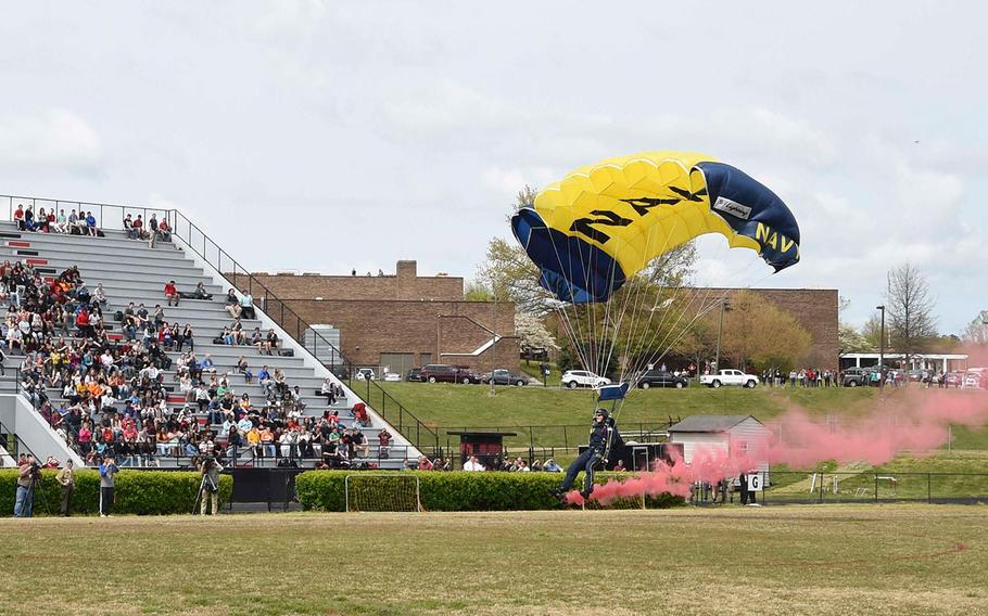 Petty Officer 1st Class Remington Peters, a member of the U.S. Navy Parachute Team, the Leap Frogs, trails smoke as he prepares to land on the field at Central High School as part of Knoxville Navy Week on April 13, 2016.