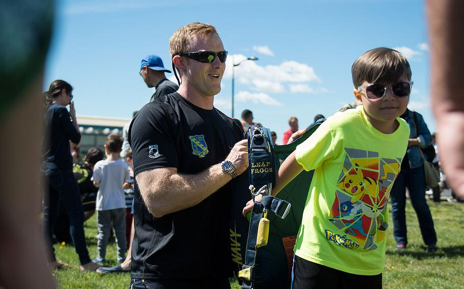 """Petty Officer 1st Class Remington Peters, a member of the U.S. Navy Parachute Team """"The Leap Frogs,"""" helps a young fan try on a parachute at Eisenhower Park during Fleet Week New York on May 27, 2017."""