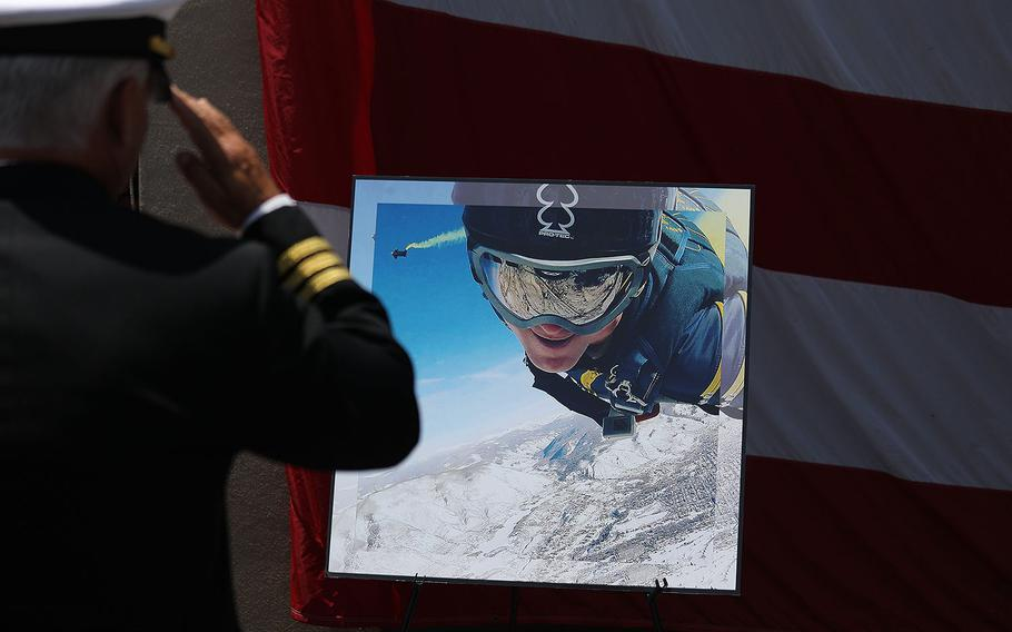 A Navy SEAL salutes a photo of Petty Officer 1st Class (SEAL) Remington Peters during his memorial ceremony at Naval Amphibious Base, Coronado on June 2, 2017.