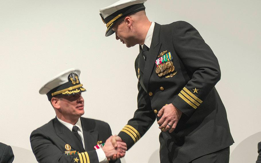 Cmdr. Steven Everhart, standing, shakes hands with Cmdr. John Cage during a change of command ceremony on Jan. 13, 2017 for the Blue crew of the Ohio-class ballistic-missile submarine USS Pennsylvania (SSBN 735).