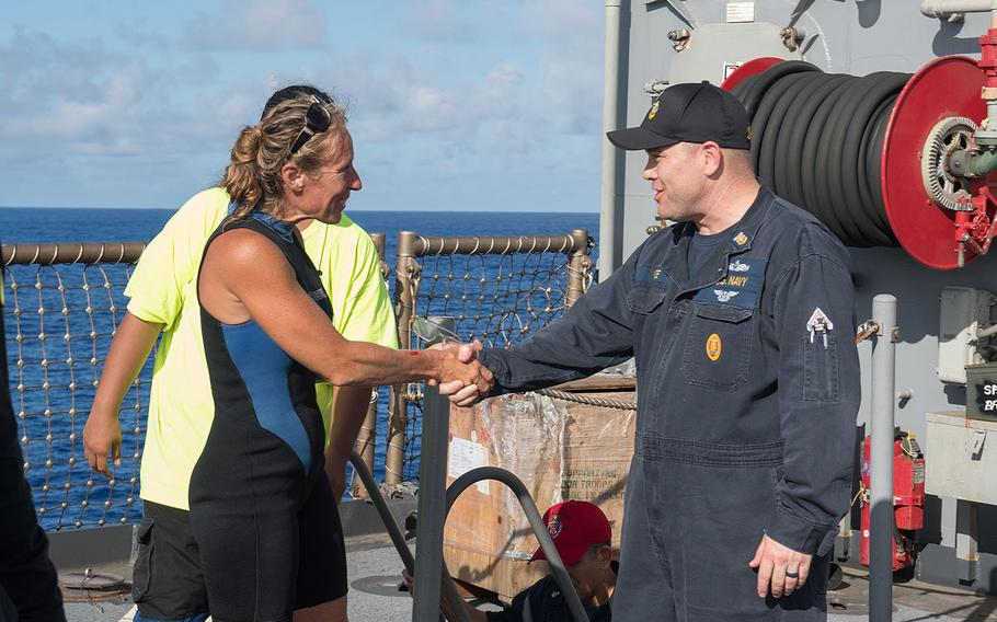 USS Ashland (LSD 48) Command Master Chief Gary Wise welcomes aboard Jennifer Appel, an American mariner who had received assistance from Ashland crew members.