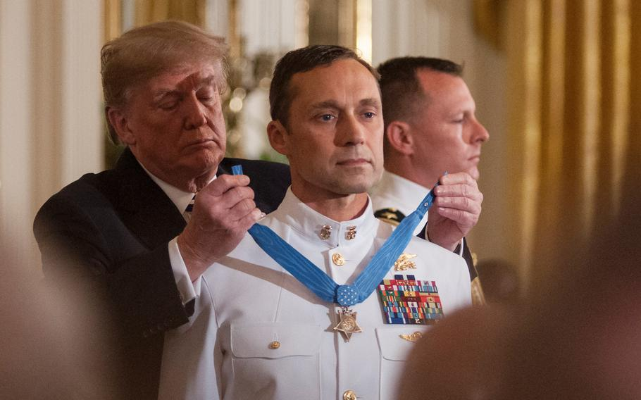 President Donald Trump presents the Medal of Honor to retired Navy SEAL Master Chief Petty Officer Britt Slabinski who was recognized for his bravery and heroic actions in what is known as the Battle of Roberts Ridge in Afghanistan in March 2002.