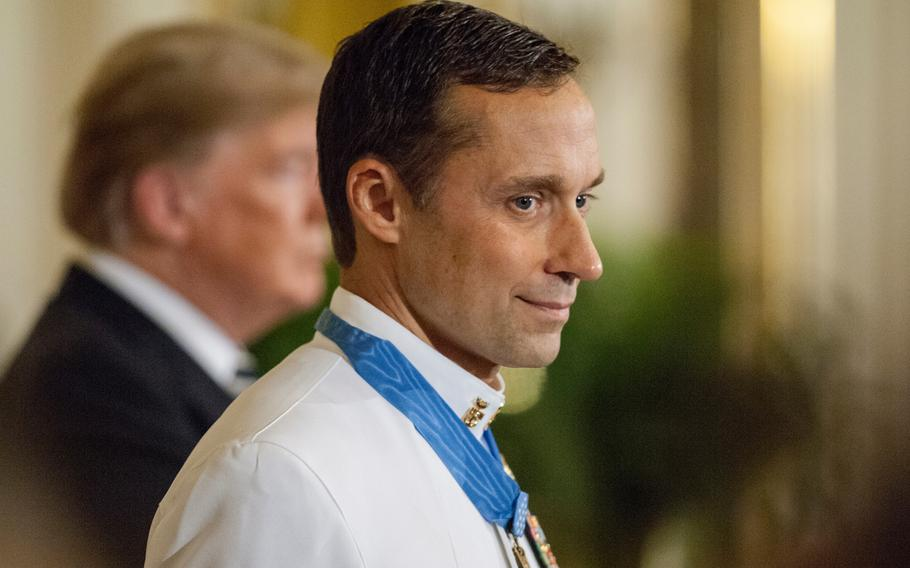 Retired Navy SEAL Master Chief Petty Officer Britt Slabinski grins as he looks towards the crowd after being presented the Medal of Honor at the White House in Washington, D.C., on Thursday, May 24, 2018, during a ceremony in which President Donald Trump, in background, recognized Slabinski for his bravery and heroic actions in what is known as the Battle of Roberts Ridge in Afghanistan in March 2002.