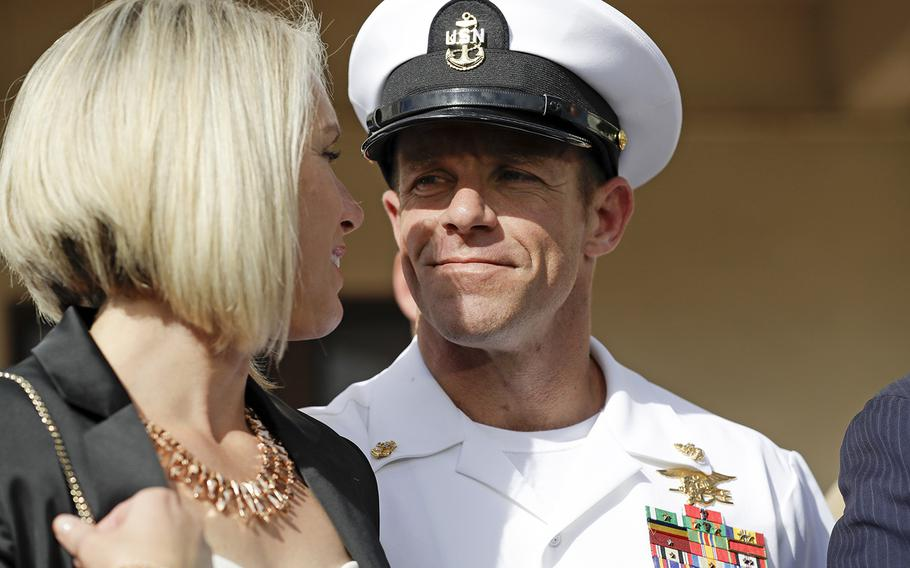 In this July 2, 2019 photo, Navy Special Operations Chief Edward Gallagher, right, walks with his wife, Andrea Gallagher as they leave a military court on Naval Base San Diego, in San Diego.