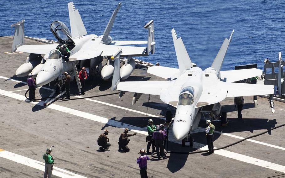 In a July 31, 2019 photo, sailors pre-check F/A-18 Super Hornets prior to flight operations on the flight deck of the USS Harry S. Truman during training in the Atlantic Ocean.