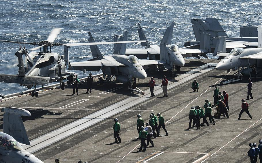 """An MH-60R Sea Hawk helicopter, attached to the """"Proud Warriors"""" of Helicopter Maritime Strike Squadron (HSM) 72, lands on the flight deck of the USS Harry S. Truman while transiting the Bab al-Mandeb Strait on Dec. 17, 2019. The Navy had planned to decommission the carrier in 2024, but reversed that decision."""