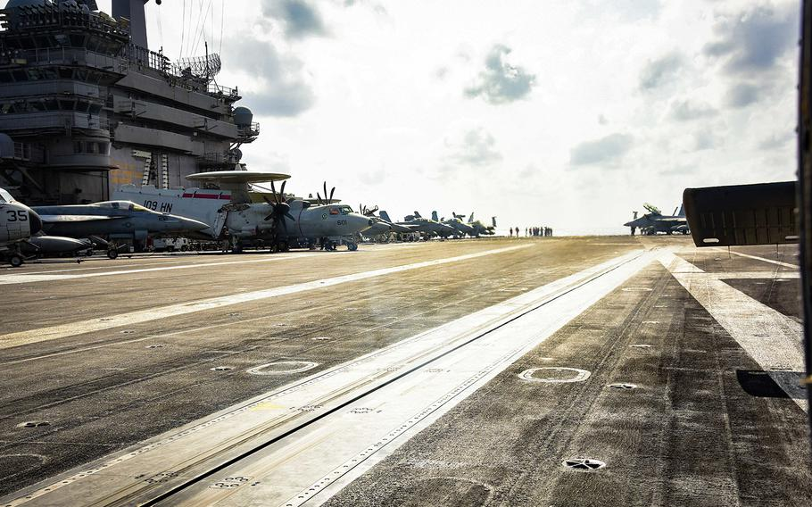 Sailors work on the flight deck of the USS Theodore Roosevelt (CVN 71) March 18, 2020, while transiting the Philippine Sea. On Wednesday, April 1, the Navy said it is working to move most of the crew off the aircraft carrier because of a coronavirus outbreak on the ship.