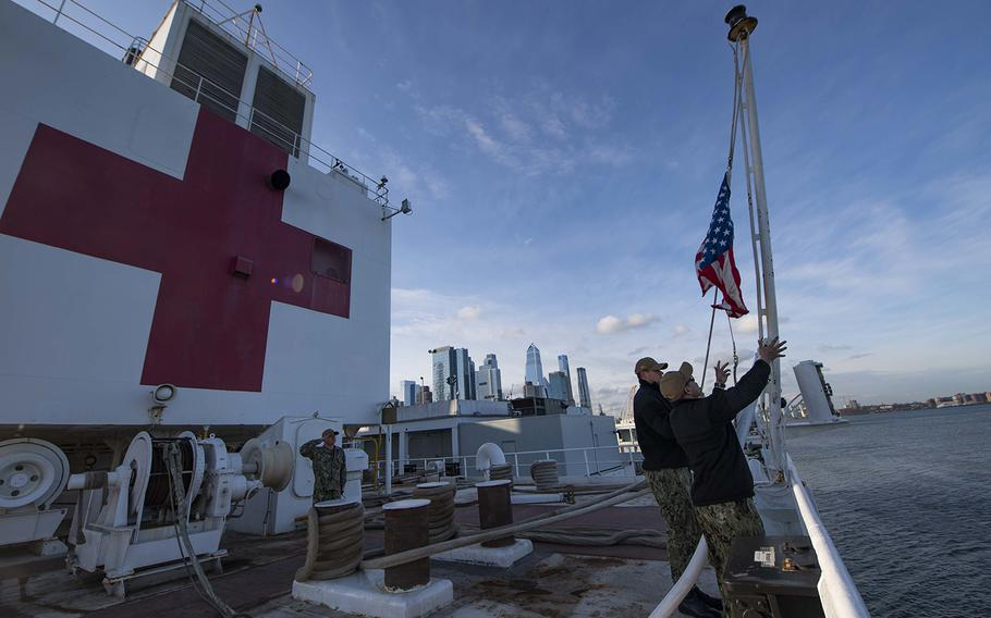 Sailors participate in a morning colors ceremony aboard the hospital ship USNS Comfort on April 1, 2020, while the ship is moored in New York City in support of the nation's COVID-19 response efforts.