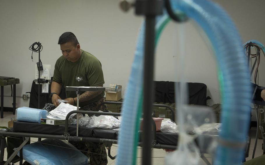 U.S. Navy Petty Officer 3rd Class Adan Trinidad, an intensive care unit medic with 3rd Medical Battalion, 3rd Marine Logistics Group, prepares an intensive care unit bed as part of transitioning an empty building into an operationally capable ICU in order to provide medical support to any USS Theodore Roosevelt sailors in need at Naval Base Guam on April 5, 2020.