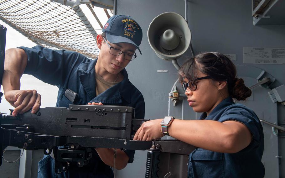 Gunner's Mate Seaman Jose Garciaflores and Gunner's Mate 3rd Class Anne Canta work on a .50-caliber machine gun aboard the USS America in the Philippine Sea on April 8, 2020.