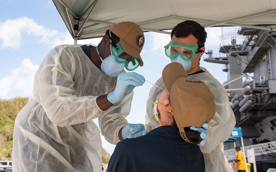 Christian Akins, left, from Atlanta, and Austin Brunt, from Charleston, S.C., assigned to Naval Hospital Guam, take a nasal sample from a U.S. sailor assigned to the aircraft carrier USS Theodore Roosevelt (CVN 71) as part of a public health outbreak investigation on April 23, 2020.