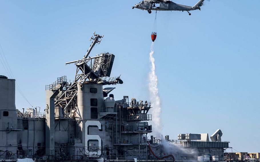 """An MH-60S Sea Hawk helicopter from the """"Merlins"""" of Helicopter Sea Combat Squadron 3 provides aerial firefighting support to fight the fire aboard the amphibious assault ship USS Bonhomme Richard."""