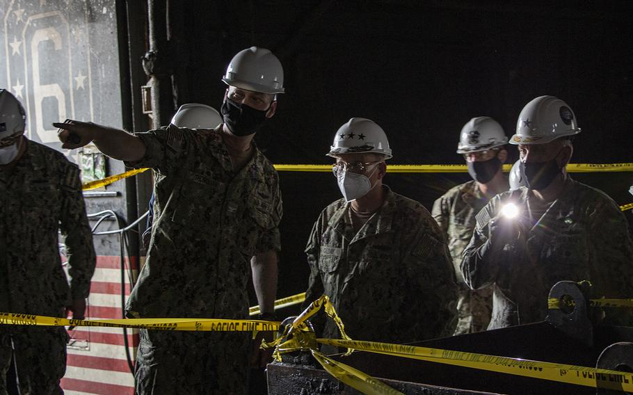 Capt. G.S. Thoroman, left, commanding officer of amphibious assault ship USS Bonhomme Richard (LHD 6) points out fire damage in the hangar bay for Chief of Naval Operations (CNO) Adm. Mike M. Gilday during a visit to the ship on July 17, 2020, to address the crew and assess fire damage.