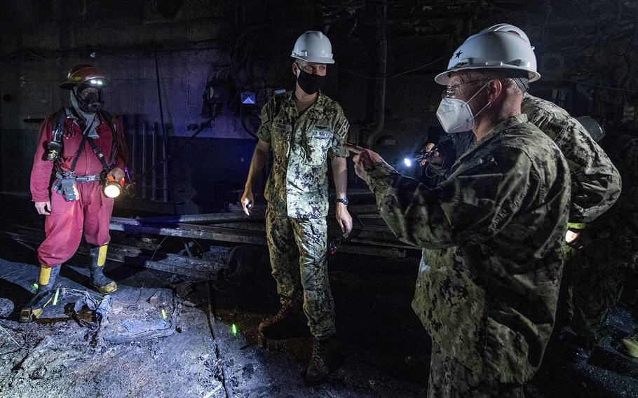 Chief of Naval Operations Adm. Mike Gilday, right, walks through the amphibious assault ship USS Bonhomme Richard (LHD 6) on July 17, 2020, to assess fire damage.
