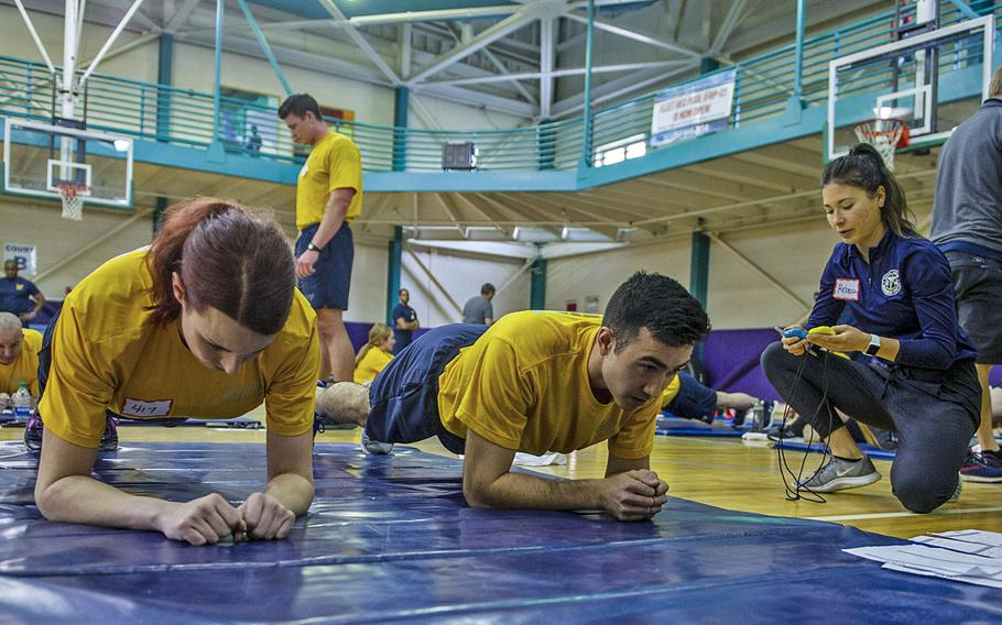 In a March 10, 2020 photo, an instructor explains the proper technique for a plank as part of a Navy Physical Readiness Test Evaluation Phase at Naval Station Norfolk, Va.