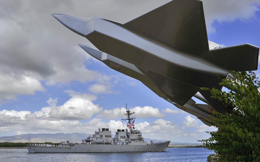 The guided-missile destroyer USS Hopper passes the Missing Man Formation Memorial on its way to Joint Base Pearl Harbor-Hickam, Hawaii, in 2014.