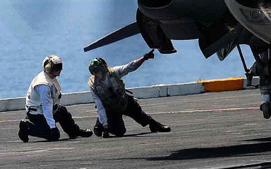 An aviation machinist's mate, right, walks a hospital corpsman through a pre-flight inspection of an E-2C Hawkeye aboard the aircraft carrier USS Ronald Reagan. The Ronald Reagan Carrier Strike Group is operating in the western Pacific Ocean. The Navy announced Thursday that it would be cutting 3,000 sailors in the ranks of E-4 to E-8 from overmanned career fields, such as the  aviation machinist's mate rating.
