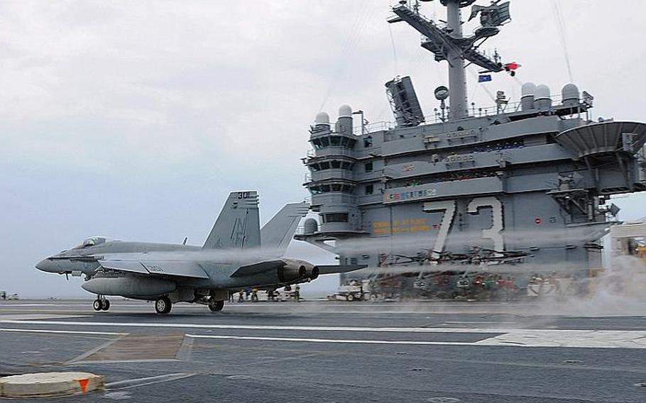 An F/A-18E Super Hornet assigned to the Eagles of Strike Fighter Squadron 115 conducts a touch-and-go landing aboard the aircraft carrier USS George Washington.