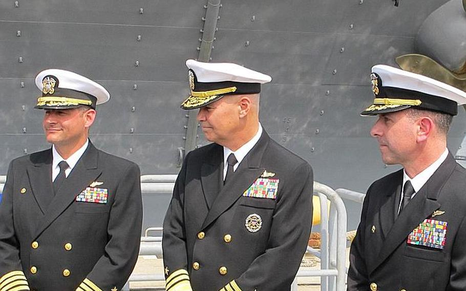 From left to right, Capt. Chuck Litchfield, formerly of the Bonhomme Richard, Vice Admiral Richard W. Hunt, Commander, Naval Surface Force, U.S. Pacific Fleet, and Capt. David Fluker, formerly of the USS Essex and now of the USS Bonhomme Richard. Fluker and Litchfield swapped ships April 23, 2012, during what is called a hull swap at Sasebo Naval Base.