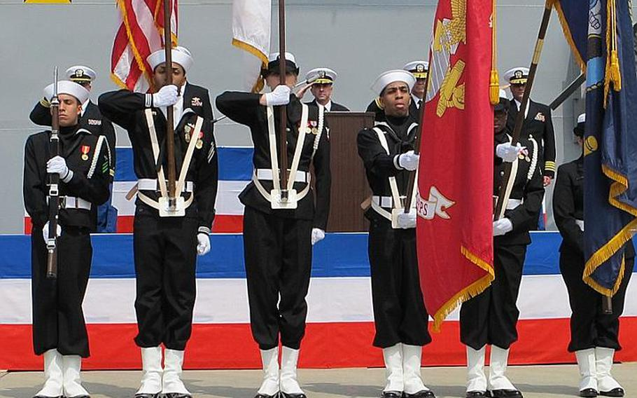 Capt. David Fluker, center, formerly of the USS Essex and now of the USS Bonhomme Richard salutes the colors April 23, 2012, during a hull swap ceremony at Sasebo Naval Base.