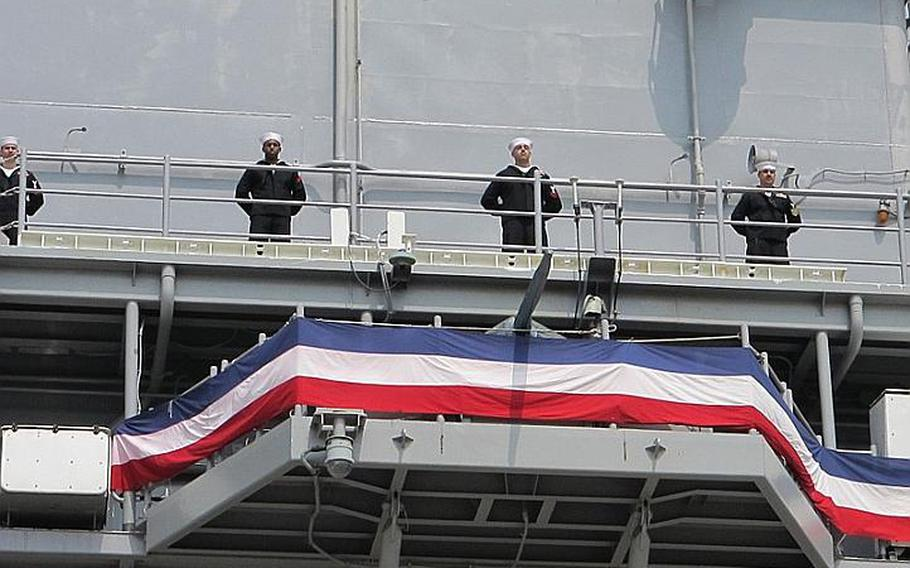 Former USS Essex sailors man the rails of the USS Bonhomme Richard following a hull swap ceremony April 23, 2012, at Sasebo Naval Base.