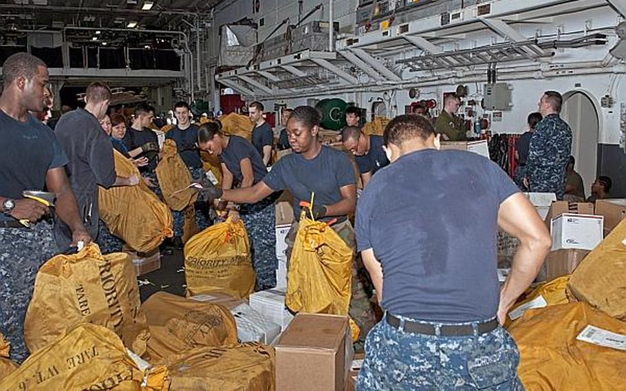 Sailors sort mail in the hangar bay of the amphibious assault ship USS Peleliu (LHA 5) during a replenishment at sea March 17 in the U.S. 5th Fleet area of responsibility.