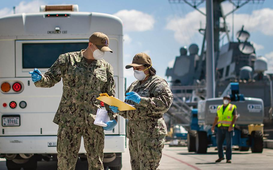Sailors check muster sheets May 18, 2020, during a crew swap for the USS Kidd, docked in San Diego, in the next phase of the Navy's plan to eradicate the coronavirus from the ship and crew.