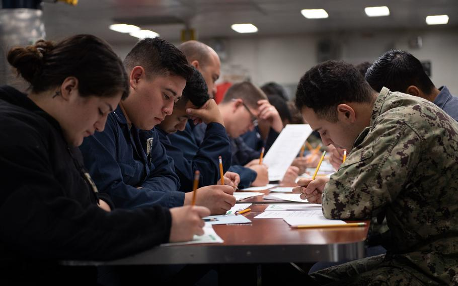 Sailors aboard amphibious assault ship USS Boxer take the navy-wide E-5 advancement exam on the ships mess decks in March 2020 in San Diego. The Navy has canceled fall Petty Officer 3rd Class advancement exams to limit exposure to coronavirus.
