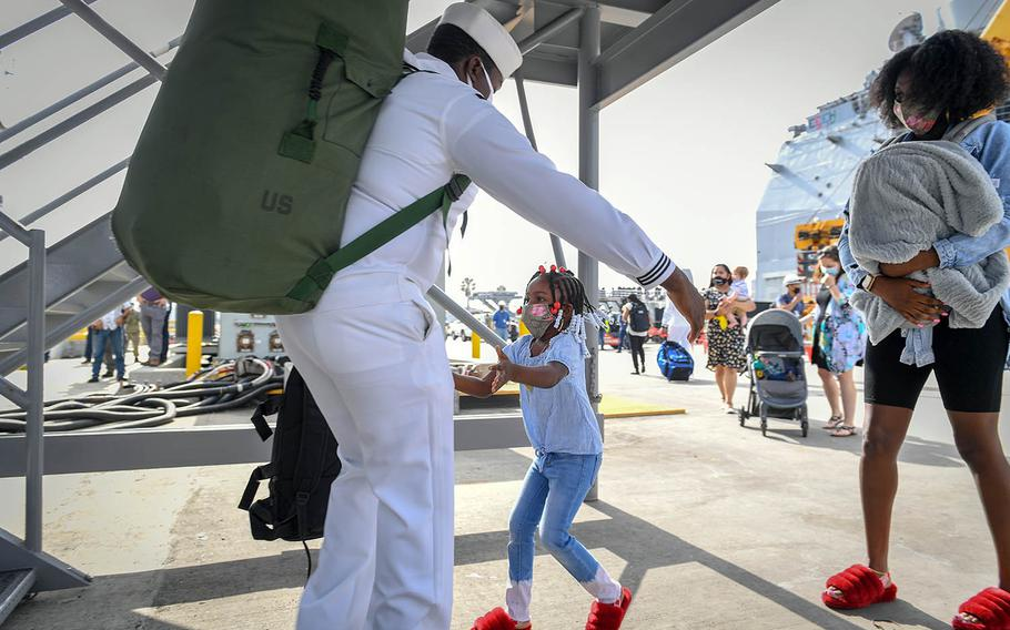 A sailor greets his family at Naval Base San Diego, July 8, 2020, after returning from a six-month deployment aboard the guided-missile cruiser USS Bunker Hill.
