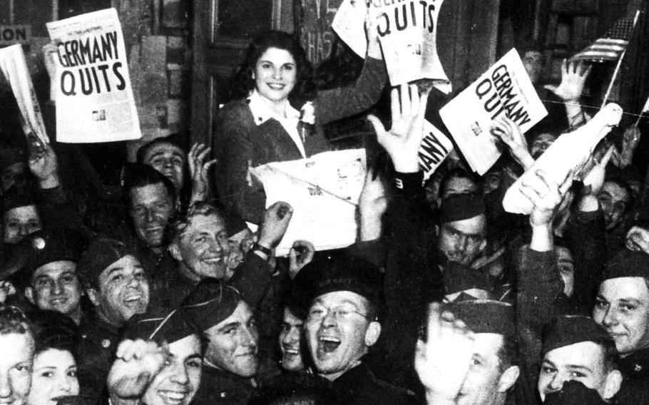 Victory in Europe day celebration. The revelers hold a copy of the May 8, 1945, London edition of the Stars and Stripes.