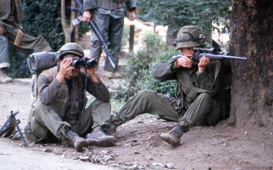A Marine sniper takes aim from behind a tree as his comrade looks through a pair of binoculars to establish the enemy position in Hue during the battle for the city in 1968.