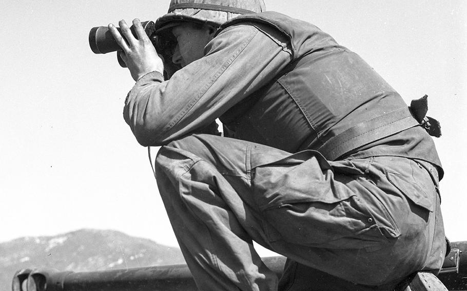 Pvt. Oliver F. Wise of Ironton, Ohio, a member of the 245th Tank Battalion, scans enemy terrain with binoculars before his tank opens fire on North Korean bunkers opposite Sandbag Castle in April, 1953.