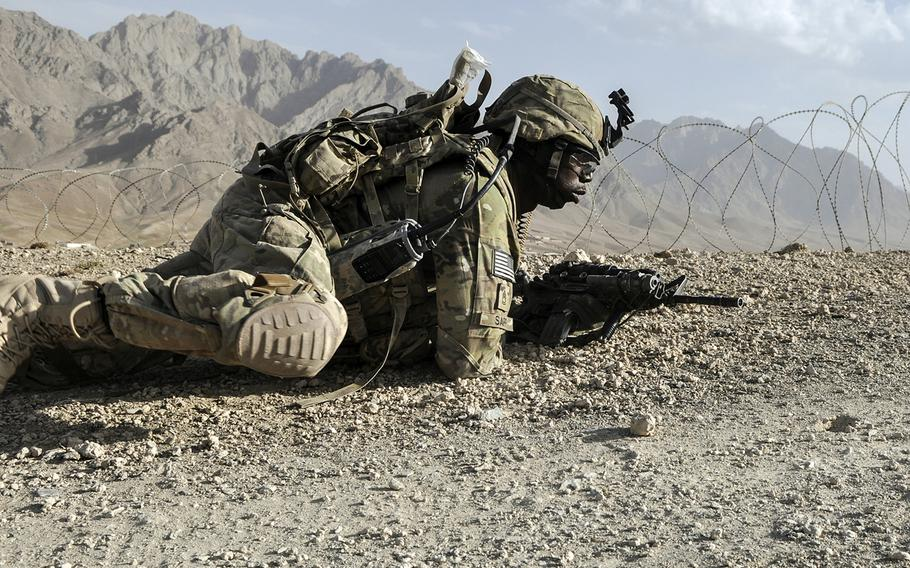 107p cs Sgt. 1st Class Trederick Sapp, of Headquarters and Headquarters Company, 4th Brigade of the 10th Mountain Division, crawls toward the camp perimeter to scan for insurgents after a firefight .   Neil Shea/Stars and Stripes