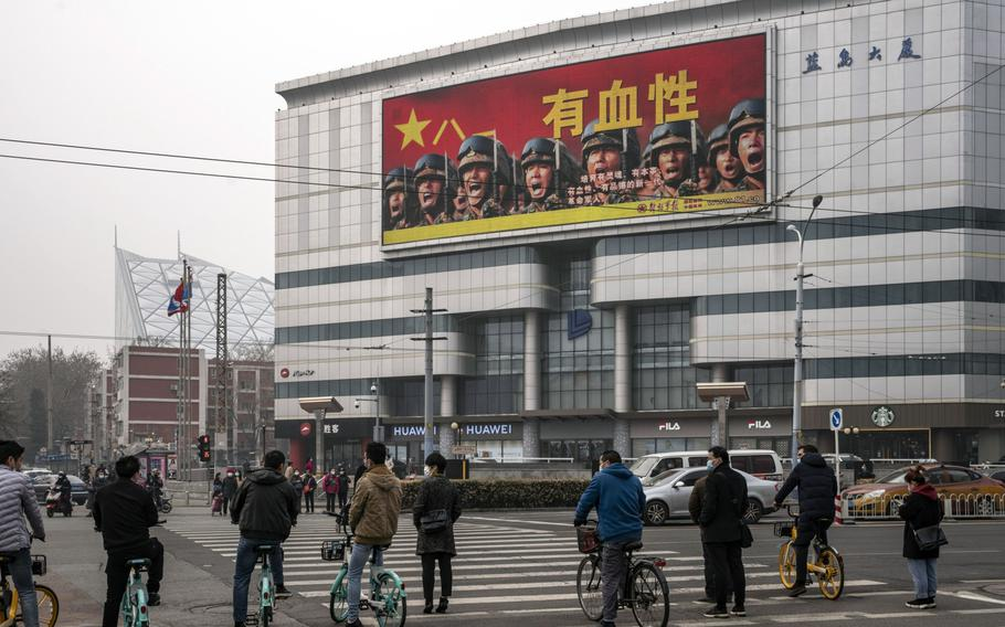 Pedestrians and cyclists stand in front of a screen showing an advertisement for the People's Liberation Army in Beijing on March 5, 2021.