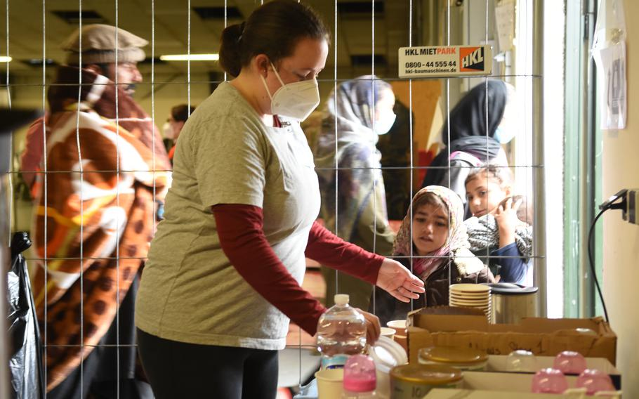 Volunteer Erin Shah grabs a lid at the formula and tea station at Rhine Ordnance Barracks, Germany, on Sept. 20, 2021. Afghan children watch intently while she works.