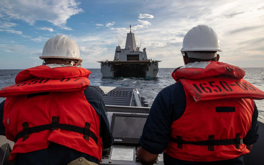 Chief Quartermaster Jesse Glover, left, and Boatswain's Mate 1st Class Diony Angeles assigned to Beach Master Unit 2 maneuver a landing craft, utility into the well deck of the San Antonio-class amphibious transport dock ship USS Arlington on Aug. 18, 2021. Arlington is deployed to U.S. Naval Forces Southern Command/U.S. 4th Fleet to support humanitarian assistance and disaster relief efforts in Haiti.