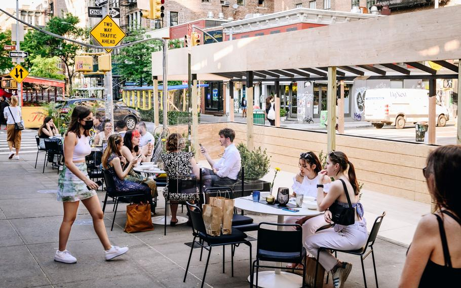 Pedestrians sit in the outdoor dining section of a restaurant in the SoHo neighborhood of New York on May 19, 2021.